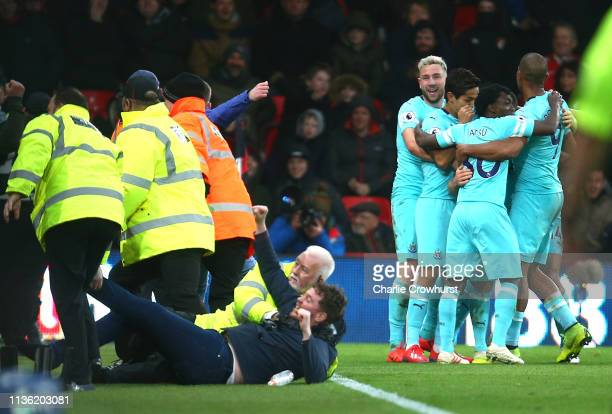 Stewards tackle a pitch invader as Matt Ritchie of Newcastle United celebrates with teammates after scoring his team's second goal during the Premier...