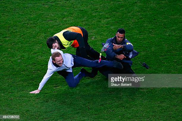 Stewards tackle a pitch invader during the 2015 Rugby World Cup Semi Final match between Argentina and Australia at Twickenham Stadium on October 25...