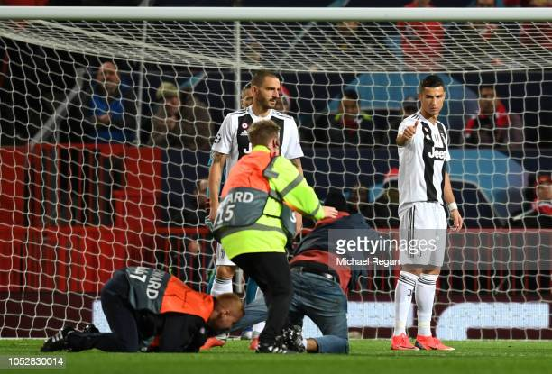 Stewards tackle a pitch invader who runs towards Cristiano Ronaldo of Juventus during the Group H match of the UEFA Champions League between...