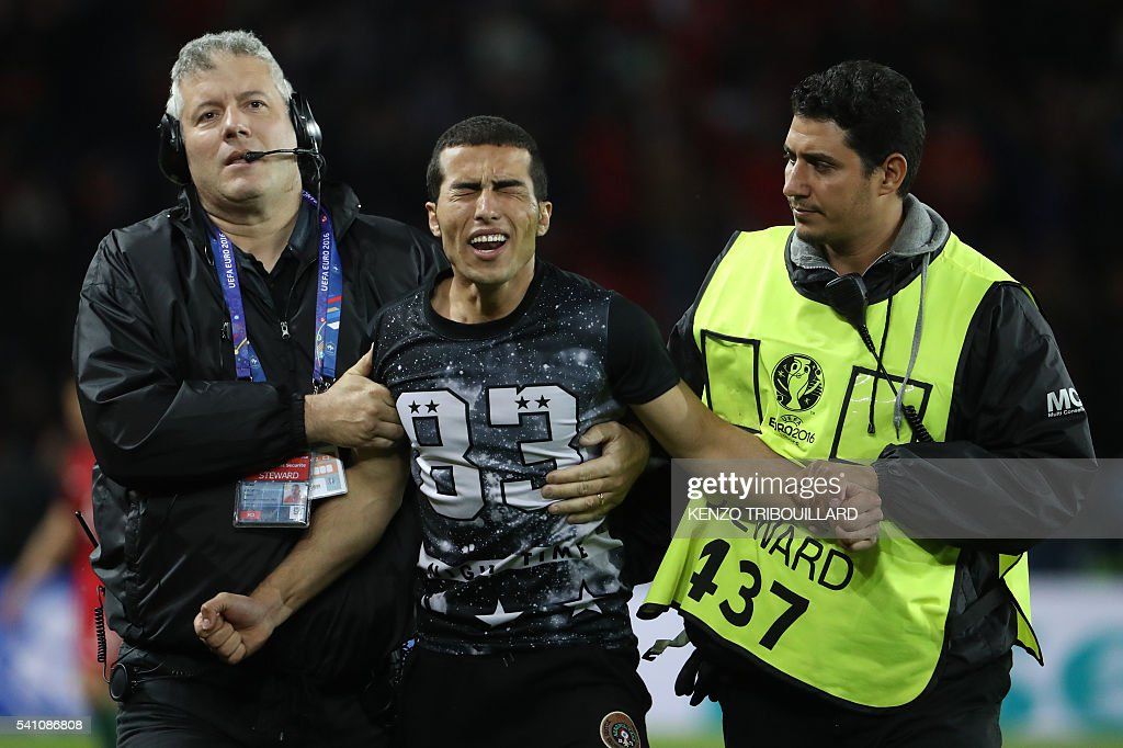 TOPSHOT - Stewards take a fan out of the pitch after greeting Portugal's forward Cristiano Ronaldo at the end of the Euro 2016 group F football match between Portugal and Austria at the Parc des Princes in Paris on June 18, 2016. / AFP / KENZO