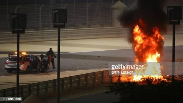 Stewards watch as Haas F1's French driver Romain Grosjean's car burns during the Bahrain Formula One Grand Prix at the Bahrain International Circuit...