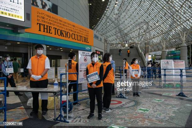Stewards wearing face masks and plastic visors wait to check the temperature of fans arriving at Tokyo Dome ahead of the Japan Central League...