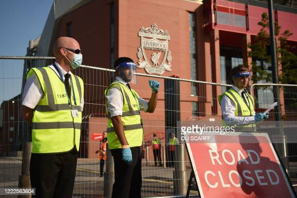 Stewards wearing face masks, shields and gloves wait outside Anfield stadium in the sunshine on the hottest day of the year ahead of the English...