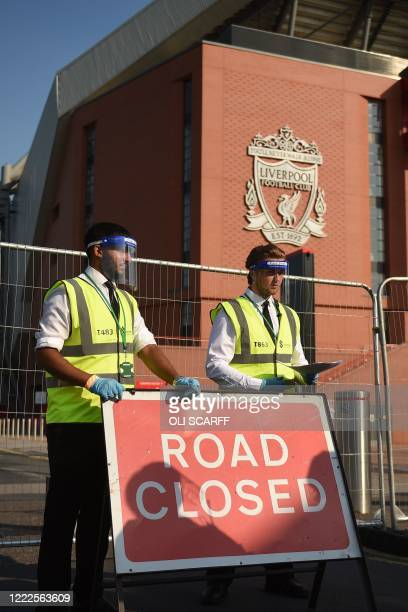 Stewards wearing face shields and gloves wait outside Anfield stadium in the sunshine on the hottest day of the year ahead of the English Premier...