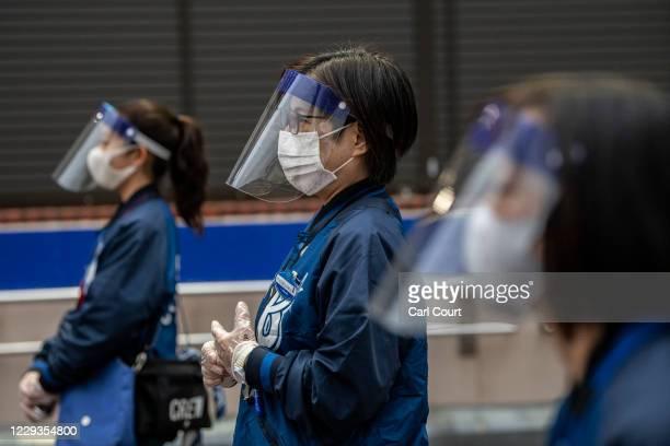 Stewards wearing plastic face visors and face masks wait to check tickets at Yokohama Stadium ahead of a baseball match between Yokohama DeNA...