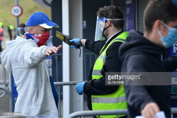 Stewards wearing PPE scan arriving supporters wearing face coverings ahead of the pre-season friendly football match between Brighton and Hove Albion...