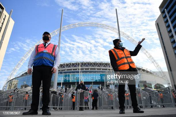 Stewards welcome spectators to attend the English FA Cup semi-final football match between Leicester City and Southampton at Wembley Stadium in north...