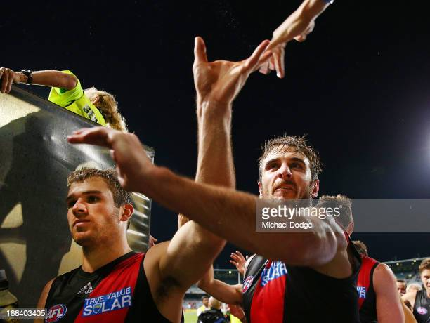 Stewart Carmeri and Jobe Watson of the Bombers celebrate the win with fans during the round three AFL match between the Fremantle Dockers and the...