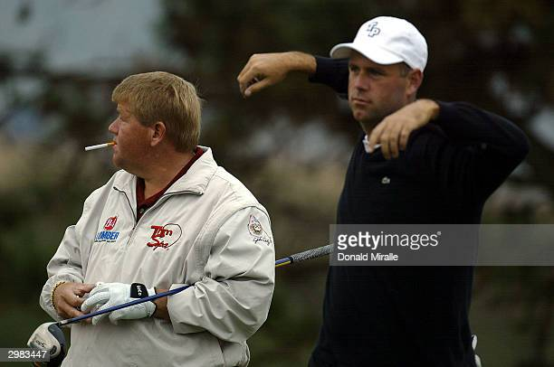 Stewart Cink stretches as John Daly lights up a cigarette as they prepare tee off the 4th hole during the 3rd round at the Buick Invitational at...