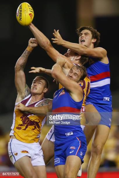 Stewart Crameri of the Bulldogs is crunched in this contest against Claye Beams of the Lions during the 2017 JLT Community Series AFL match between...