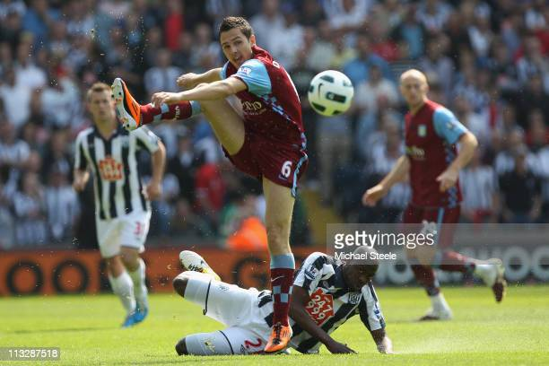Stewart Downing of Villa hurdles above the challenge from Youssouf Mulumbu during the Barclays Premier League match between West Bromwich Albion and...