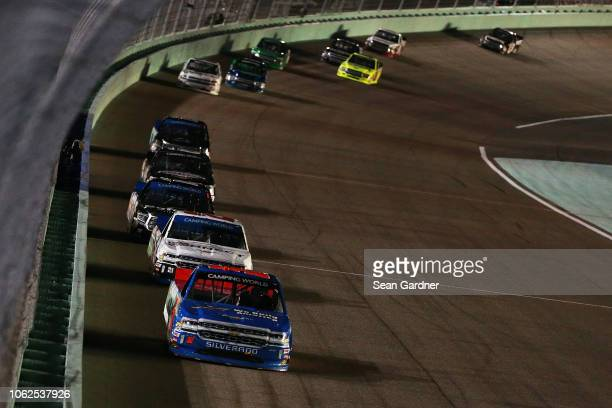 Stewart Friesen driver of the We Build America Chevrolet leads Johnny Sauter driver of the ISM Connect Chevrolet and Noah Gragson driver of the...