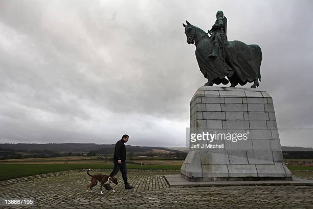 Stewart Gibson and his dog Cooper walk past a statue of Robert the Bruce situated on the site of the battle of Bannockburn on January 10 2012 in...