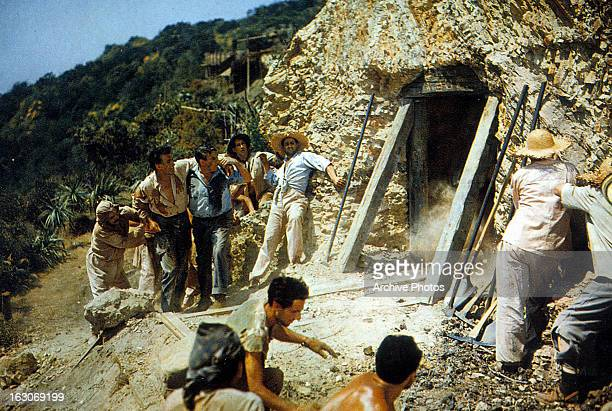 Stewart Granger and other stand outside of a mine in a scene from the film 'Green Fire' 1954