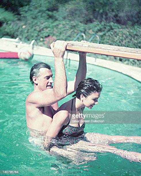 Stewart Granger British actor with his wife Jean Simmons British actress in a swimming pool with Granger holding on to the diving board circa 1955