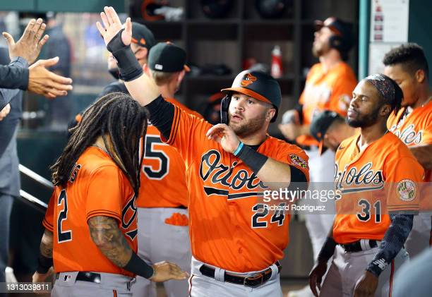 Stewart of the Baltimore Orioles is greeted in the dugout after scoring on a double by Trey Mancini in the eighth inning of the MLB game against the...