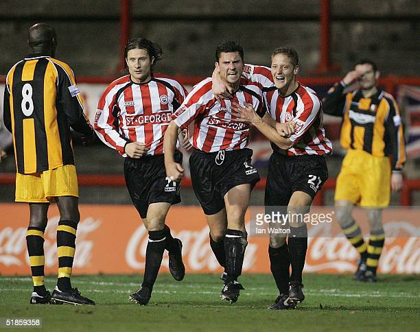 Stewart Talbot celebrates scoring his teams second goal with Chris Hargreaves and Ben May of Brentford during the FA Cup second round replay match...