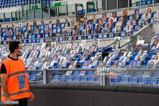 A stewart views photos of Lazio supporters placed in empty tribunes prior to the Italian Serie A football match Lazio vs Fiorentina played on June 27...