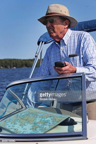 Stewart Woodworth uses a handheld GPS device with a more traditional map on the dashboard as he pilots a boat around Lake Winnipesaukee in New...