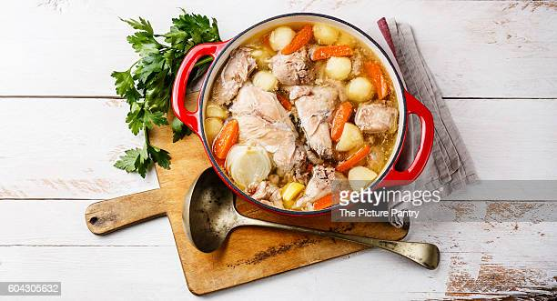 Stewed rabbit with potatoes and carrot in cast iron pot on rustic wooden table background