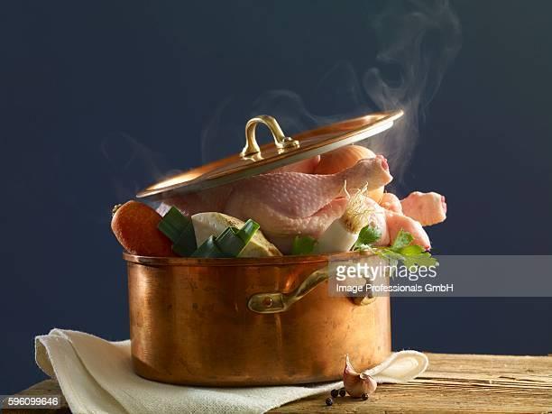 stewing chicken with vegetables in a copper pot - caldo pollo fotografías e imágenes de stock