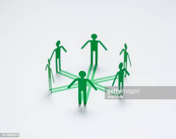 Stick figures forming a circle (paper cutout)
