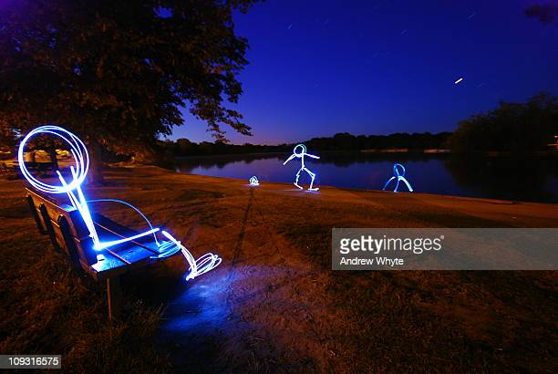 Stick men by the lake drawn with light