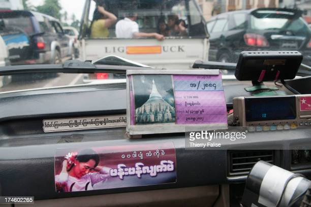 A sticker bearing a portrait of Aung San Suu Kyi is stuck on the dashboard of a taxi in Yangon
