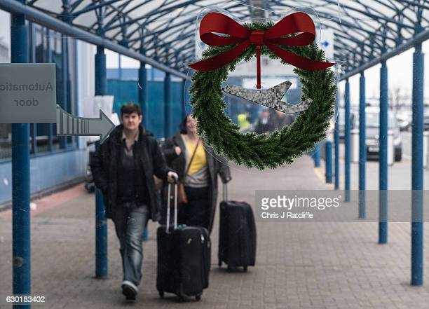 A sticker of a Christmas wreath and an airplane on the entrance door to London City Airport as passengers arrive where there are delays and...
