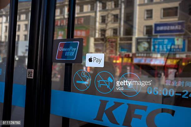 A sticker of Apple Pay is seen with the sticker of China UnionPay on a glass door of KFC on February 18 2016 in Beijing China Apple CEO Tim Cook has...