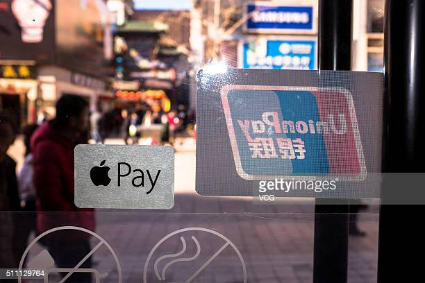 A sticker of Apple Pay is seen with the sticker of China UnionPay on a glass door on February 18 2016 in Beijing China Apple CEO Tim Cook has today...