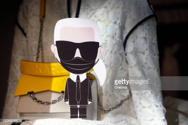 A sticker representing the famous fashion designer Karl Lagerfeld with a facial protection mask is stuck on the window of a Karl Lagerfeld store as...