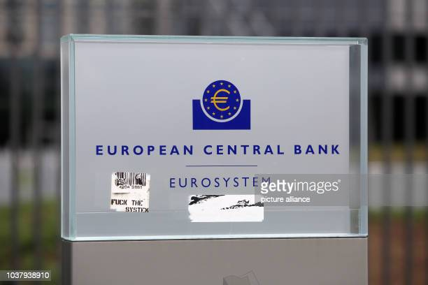 A sticker which reads 'Fuck the System' sticks to the entrance sign of the European Central Bank at the institution's headquarter in Frankfurt...