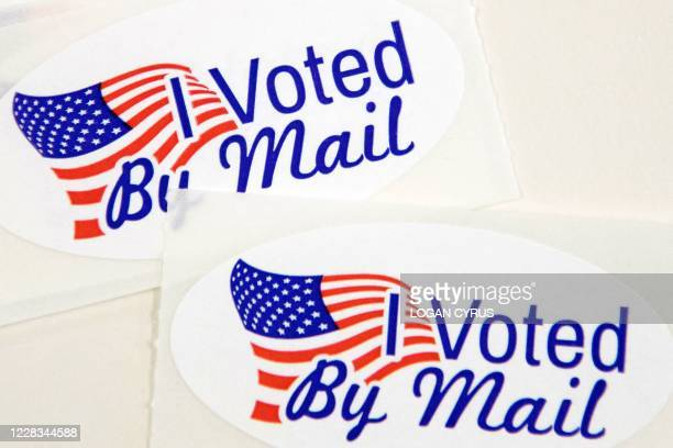 "Stickers that read ""I Voted By Mail"" sit on a table waiting to be stuffed into envelopes by absentee ballot election workers at the Mecklenburg..."