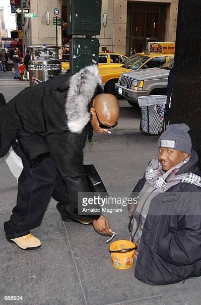 'Sticky Fingers' a member of the Hip Hop group Onyx gives twenty dollars to homeless man Byron Breeze December 24 2001 in New York City