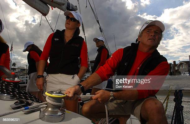 Still at the dock aboard the sailboat Cha Cha Cha out of Newport beach skipper Larry Walter explains to crew member Sarah Angel steps to jib the...
