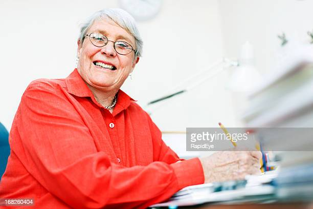 Still busy at 70, smiling woman works in office