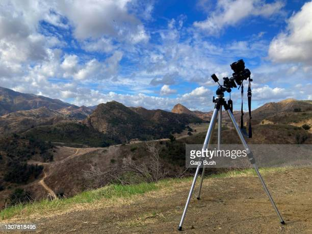 a still camera on a tripod pointing up to a beautiful blue sky with puffy clouds and mountains in the background. - 三脚 ストックフォトと画像