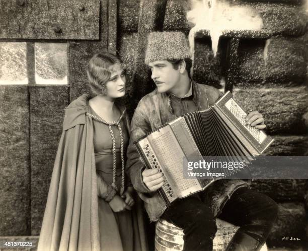 A still from the film 'Hearts in Exile' in which actor Grant Withers serenades actress Dolores Costello on an accordion 1929 Photo by Mack Elliott