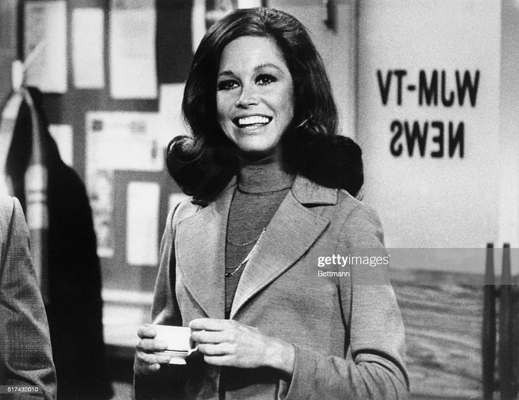 Still from The Mary Tyler Moore Show showing Moore standing, smiling, inside of the WJM newsroom. Moore is shown from the waist-up, holding a cup of coffee, circa 1975.