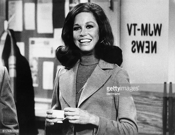 Still from The Mary Tyler Moore Show showing Moore standing, smiling, inside of the WJM newsroom. Moore is shown from the waist-up, holding a cup of...