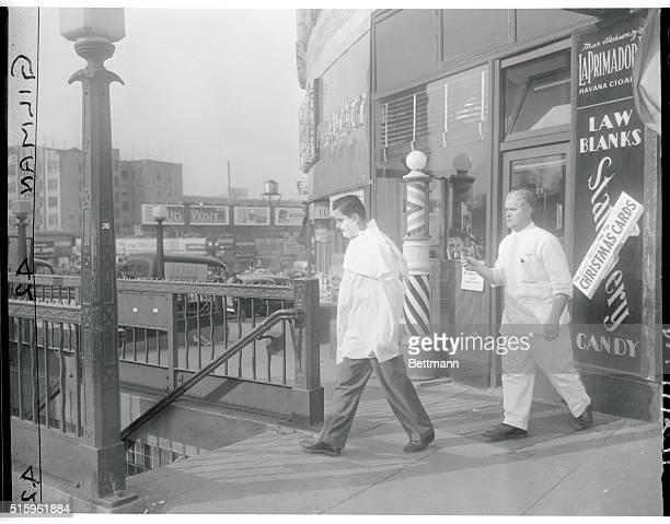 Still in lather customer Lou Cassano precedes barber Ralph Scheinholtz shop at 109 Walton Avenue Bronx to 8th Avenue subway shelter At left is...