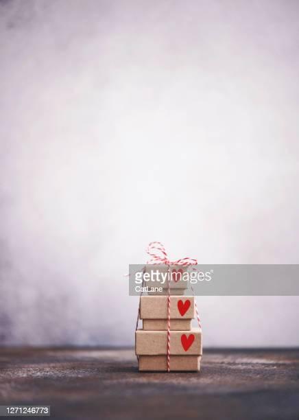 心を持つ小さな贈り物スタックの静物の背景 - 誕生日の贈り物 ストックフォトと画像