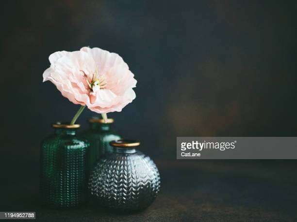 still life background with small glass jars and pink poppies - femininity stock pictures, royalty-free photos & images