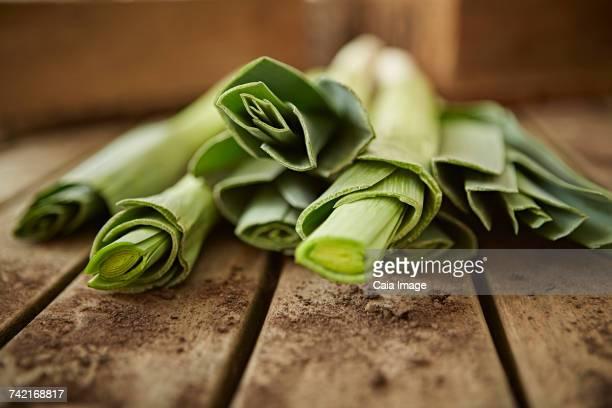Still life close up fresh, organic, healthy green leek stems on wood