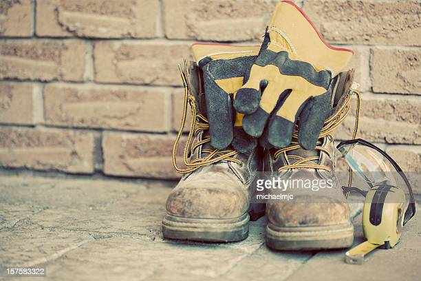 Still life containing work boots, gloves, and measuring tape