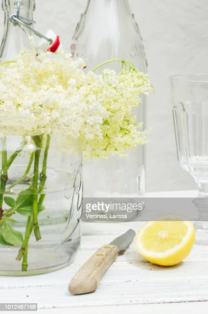 A still life featuring elderflowers, lemon, bottles and a knife