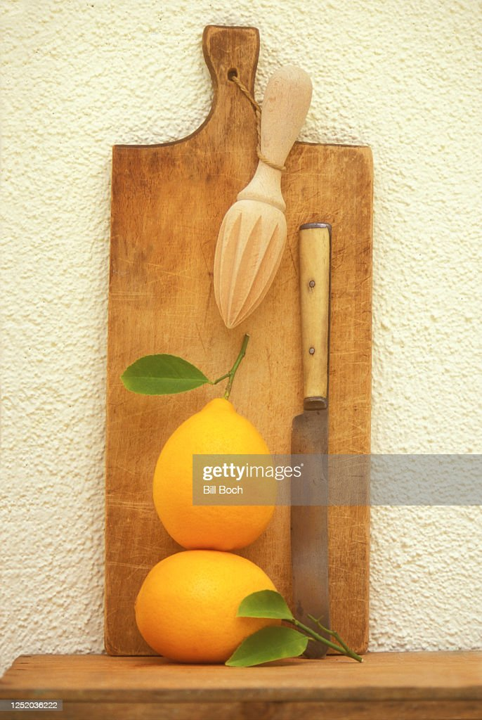 Still Life Of 2 Whole Lemons With Leaves Attached Old Cutting Board Hanging Juicer And A Antique Kitchen Knifeall On A Wood Table Leaning Against A Pale Yellow Stucco Wall High Res Stock