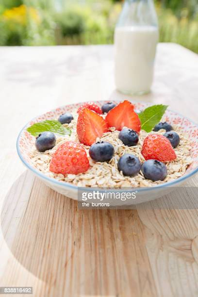 Still life of a bowl filled with porridge oats, strawberries and blueberries