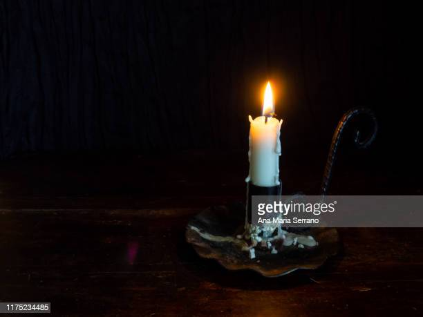 still life of a candlestick with a burning candle made of white wax on a dark wooden table. space for text - candle of hope stock pictures, royalty-free photos & images